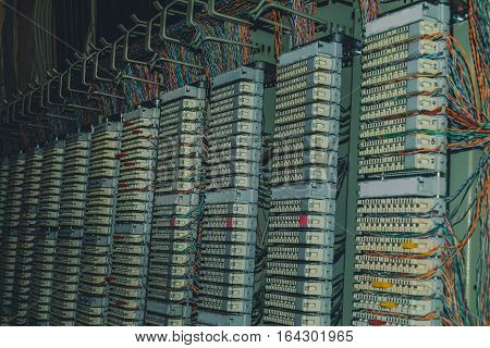 telephone patch panel in datacenter server room, a plurality of cables, cross bar