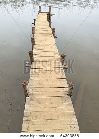 Close up of a wooden bridge in a lake