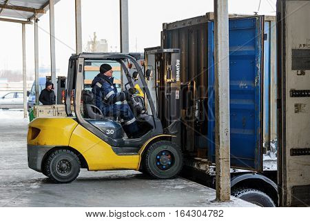 Moscow, Russia - December 13, 2016: Warehouse transport and logistics company. Forklift is putting cargo from warehouse to truck outdoors