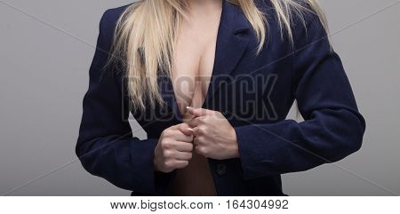 closeup on big natural sexy boobs in blue suit.
