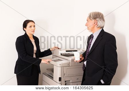 business people talking next to the copier
