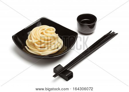 Noodles in black ceramic dish stand isolated on white background with chopsticks rest and sake cup near.