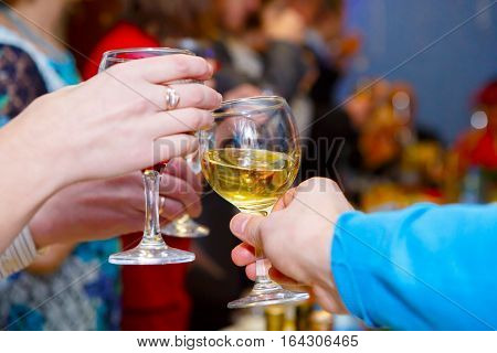 The clink of glasses at the festive table. People clink glasses together. Alcoholic feast at the Banquet. Celebration with alcohol. Joint booze at the party.