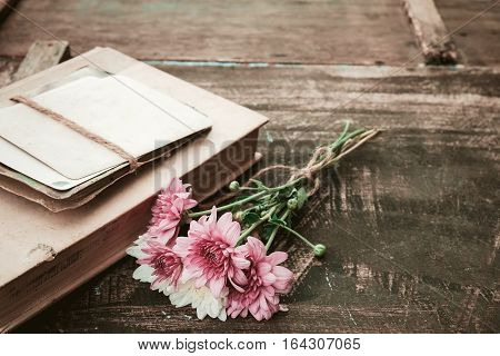 Vintage novel book with bouquet of flowers on old wood background - concept of nostalgic and remembrance in spring vintage background