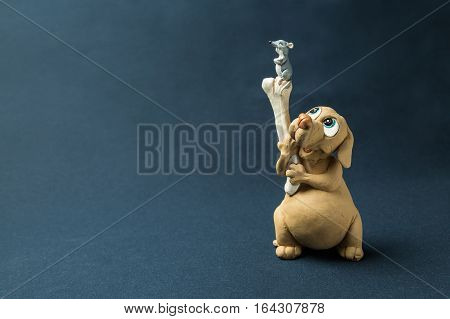 The dog holds a bone on which there is a mouse photographed against a dark background