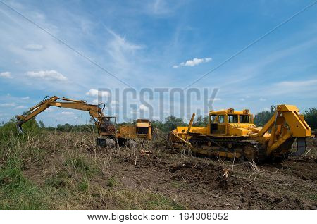Eradicating forest with a bulldozer and digger.