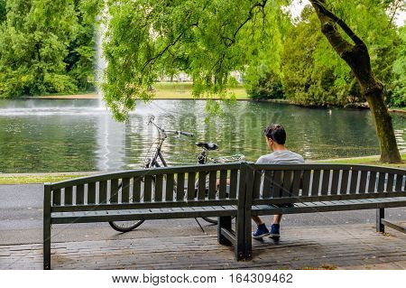 Young man day dreaming on a wooden bench in the park while he looks at the fountain in the big pond. A ladies bike is parked beside him.