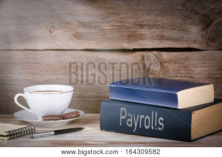 Payrolls. Stack of books on wooden desk.