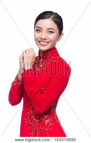 Young vietnamese woman in Ao Dai Dress with praying gesture wishing you good luck