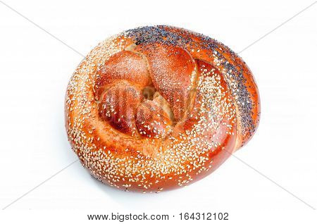Braided bun sprinkled with poppy and sesame seeds isolated on white background