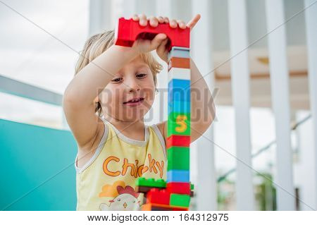 Cute Little Kid Boy Playing With Lots Of Colorful Plastic Blocks Indoor. Active Child Having Fun Wit