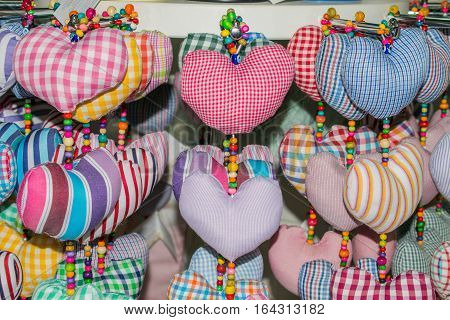 A lot of soft toys in the form of hearts from a bright and colorful fabric