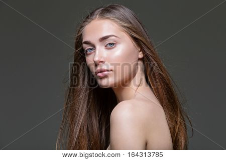 Beautiful young woman with straight healthy hair and natural make-up on dark background. Copy space.
