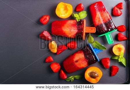 Berry and fruit ice cream pops on black surface top view
