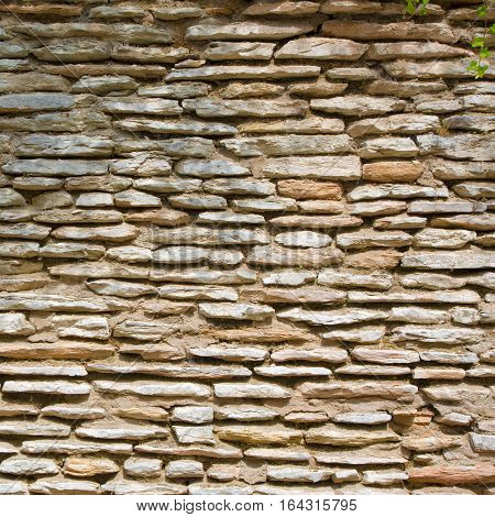 Abstract Grunge Stonewall Background. Decorative Finishing Wall Fence of Natural stone. Rough Surface Rock Texture Square Image Close up