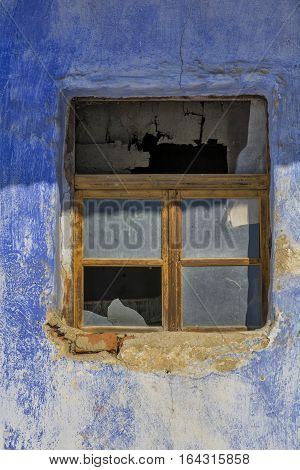 Old window frame in a vintage bricks wall in a rural romanian house. Old wall with window detail of an old building in ruins.