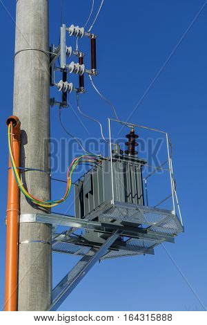 New distribution transformer on concrete power pole with external electric separator against the blue sky.