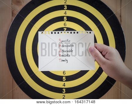 Woman hold paper handwriting SMART Goal on right hand with dart board background (Selective Focus)