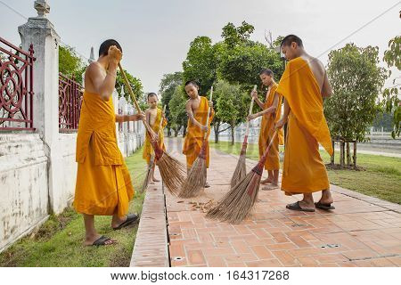 AYUTHAYA THAILAND : MARCH 28 : thai little buddhist monk daily cleaning temple area in morning routine working in wat niwesthumaprawat most famous temple in Ayuthaya Province central of thailand on march 28 2015