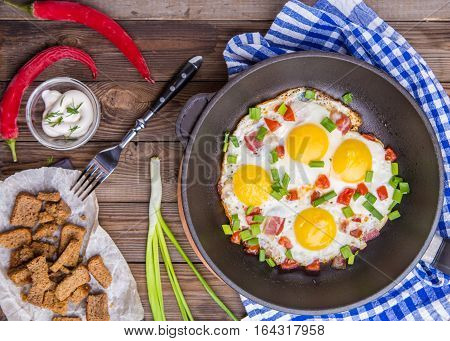 Fred eggs in pan with tomatoes and green fresh onion. Breakfast. Healthy food.