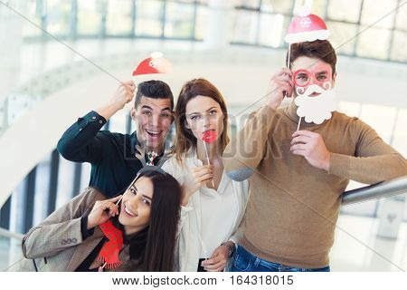 Young friends having fun holding winter artificial mustache and lips stick