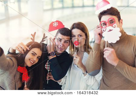 Young friends having fun holding winter artificial mustache and lips stick making selfie photo