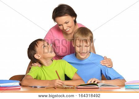 mother with sons doing homework, posing against white