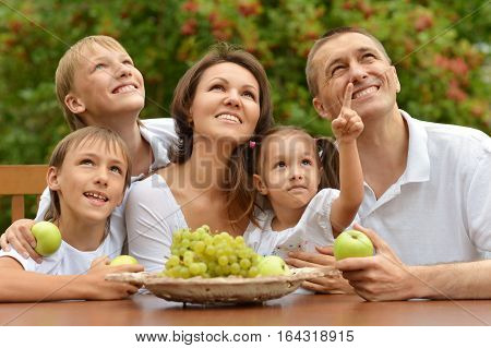 family eating fruits outdoors apples and grapes