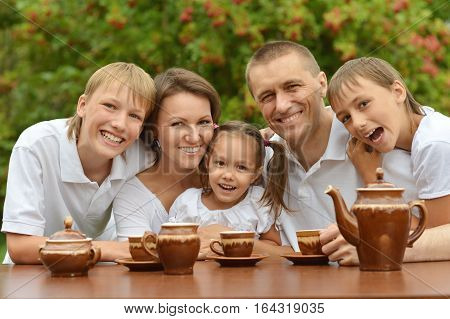 Portrait of a happy family drinking tea together outdoors