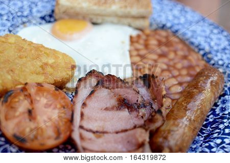 Traditional breakfast, full English, with bacon, egg, sausage, tomato, beans and hash browns with white toast