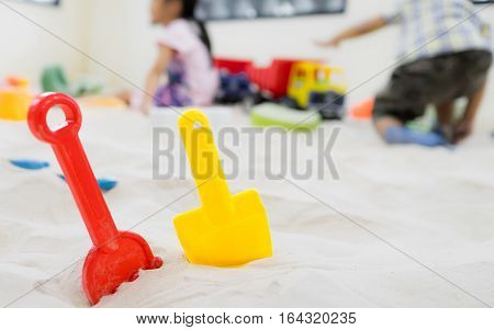 Colorful sand shovel toy with children background.