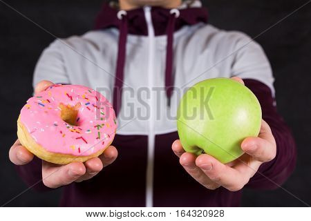 Hands choosing between apple and donut as concept of healthy and unhealthy lifestyle