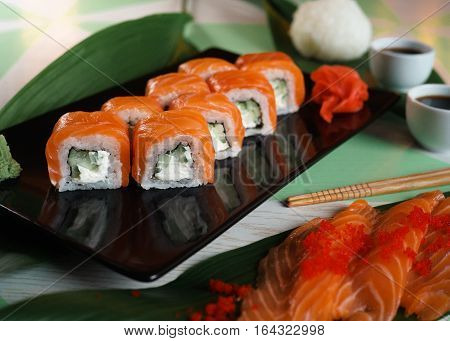 sushi with salmon and cream cheese on the black plate
