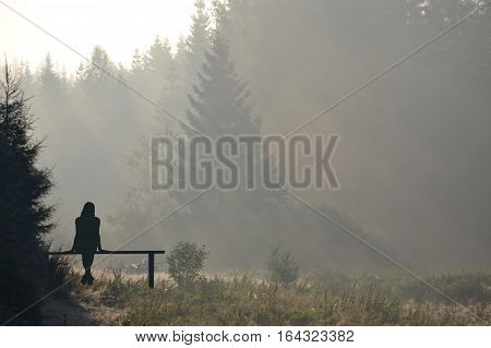Young woman silhouette relaxing on the mountains landscape in the morning