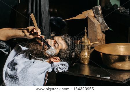 Handsome bearded man hipster brunette with beard and moustache has shave in barbershop, works with vintage razor shaving brush and foam