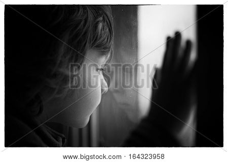a little boy looks out the window reflection Black and white