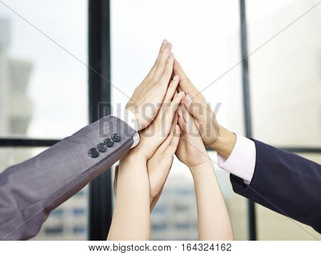business people putting hands together to form a pyramid to show determination or teamwork spirit.