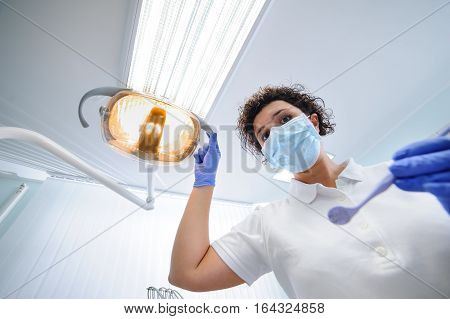 Portrait of dentist wearing surgical mask while holding dental lamp