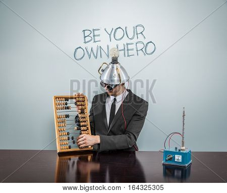 Be your own  hero text on blackboard with businessman and abacus