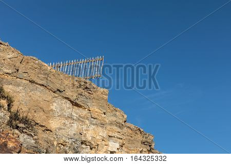 Wood fence after cliff collapse in the pointe du Payre in the ouest coast of France
