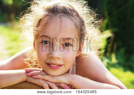 Beauty Girl Outdoors enjoying nature. Beautiful Teenage girl with long hair smiling. Happy kid. Toned in warm colors