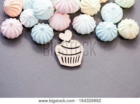 meringues in pastel colors with wooden figure of cupcake on grey background. St Valentines's Day