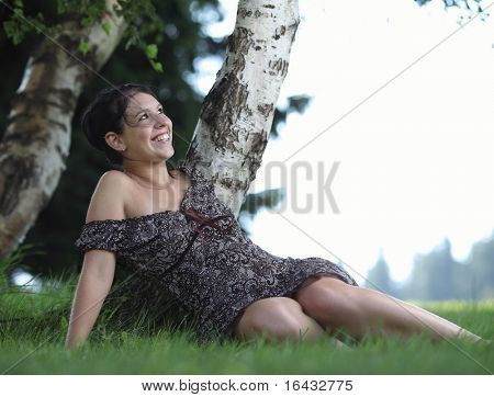 portrait of a pretty brunette sitting in a park