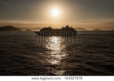 Cruise ship in navigation at sunset in backlight