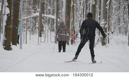 Man skier in black jacket slides in winter snow forest, telephoto