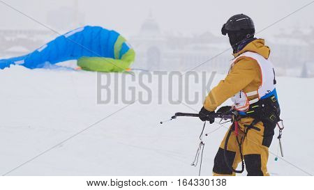 Snowkiting in the snow on frozen river, kite surfer ready for sliding, telephoto