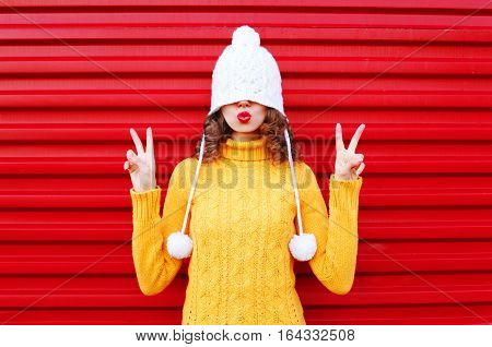 Fashion Cool Girl Blowing Red Lips Makes Air Kiss Wearing Colorful Knitted Hat, Yellow Sweater Over