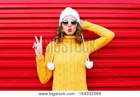 Fashion Woman Blowing Red Lips Wearing Colorful Knitted Yellow Sweater Hat Over Red Background