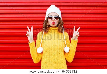 Fashion Young Woman Blowing Red Lips Wearing A Colorful Knitted Yellow Sweater Hat Over Red Backgrou