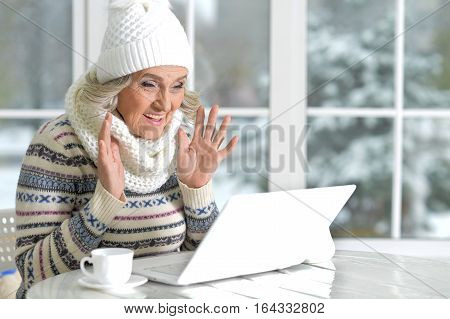 mature woman using laptop in cafe near window